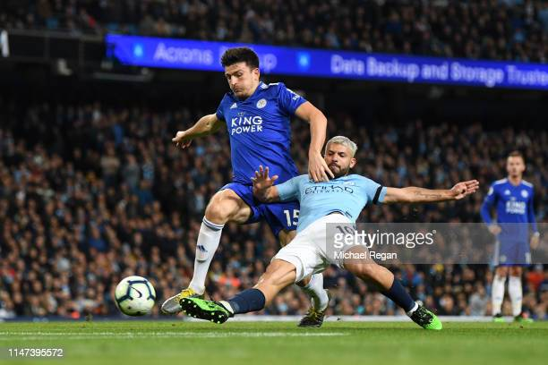 Sergio Aguero of Manchester City stretches to reach the ball as he is challenged by Harry Maguire of Leicester City during the Premier League match...