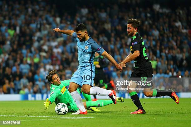 Sergio Aguero of Manchester City takes the ball past Yann Sommer of Borussia Moenchengladbach to score his and his sides third goal during the UEFA...