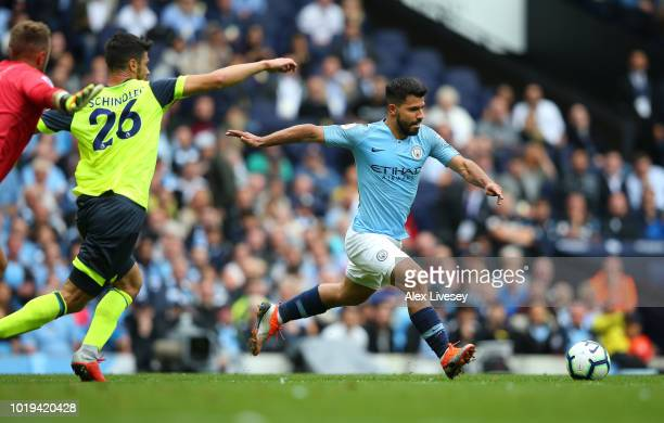 Sergio Aguero of Manchester City turns Christopher Schindler of Huddersfield Town on his way to scoring the first goal during the Premier League...