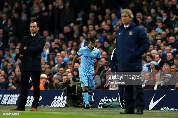 Sergio Aguero of Manchester City walks past Manuel Pellegrini manager of Manchester City as he leaves the field injured during the Barclays Premier...