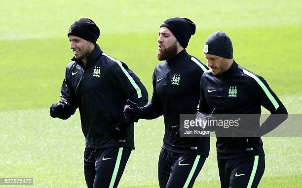 Sergio Aguero of Manchester City warms up with Nicolas Otamendi and Martin Demichelis of Manchester City during a training session ahead of the UEFA...