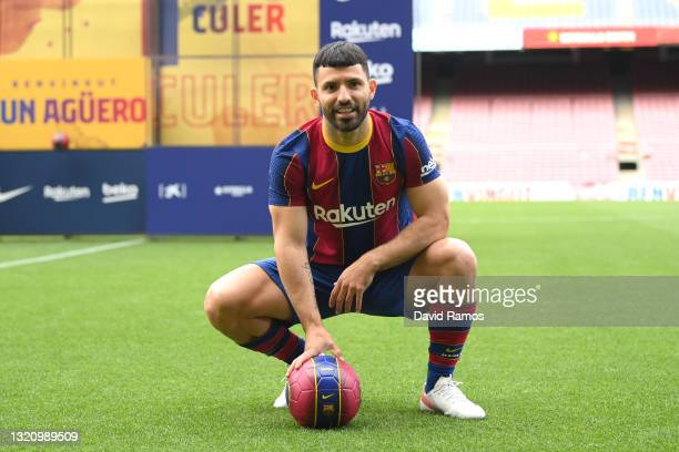 Sergio Aguero reacts whilst posing for a photograph as he is presented as a Barcelona player at the Camp Nou Stadium on May 31, 2021 in Barcelona,...