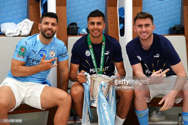 Sergio Aguero, Rodrigo and Aymeric Laporte pose for a photograph with the Carabao Cup Trophy inside the dressing room after the Carabao Cup Final...
