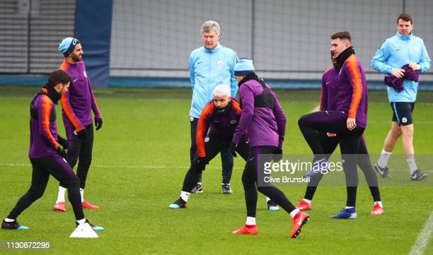 Sergio Aguero warms up with team mates as assistant manager Brian Kidd looks on during a Manchester City training session at Manchester City Football...