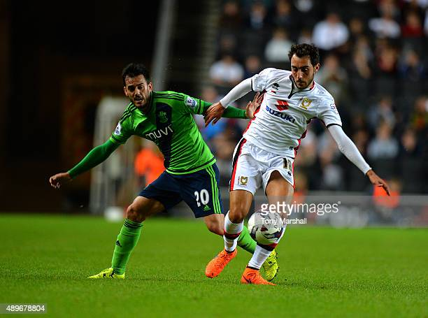 Sergio Aguza of MK Dons is tackled by Juanmi of Southampton during the Capital One Cup third round match between MK Dons and Southampton at Stadium...