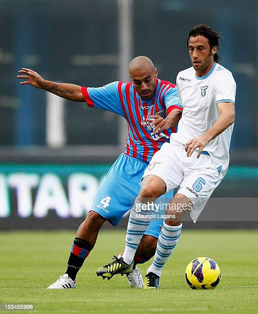 Sergio Almiron of Catania competes for the ball with Stefano Mauri of Lazio during the Serie A match between Calcio Catania and SS Lazio at Stadio...