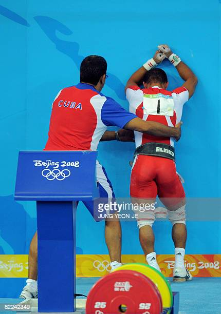 Sergio Alvarez of Cuba is consoled by a colleague after failing the lift in the men's 56 kg weightlifting event during the 2008 Beijing Olympic Games...