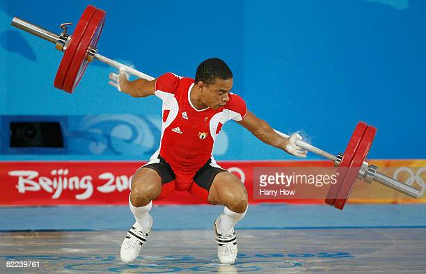 Sergio Alvarez of Cuba loses control of the bar during the men's 56kg group A weightlifting event held at the Beijing University of Aeronautics...