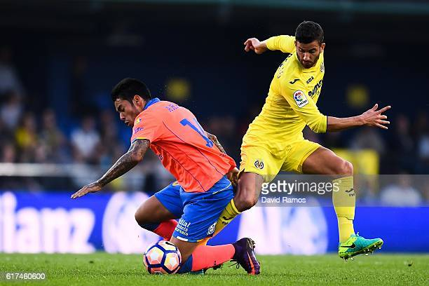 Sergio Araujo of UD Las Palmas competes for the ball with Roberto Soriano of Villarreal CF during the La Liga match between Villarreal CF and UD Las...