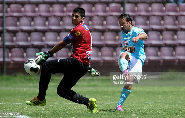Sergio Blanco of Sporting Cristal scores the opening goal against Jesus Cisneros , goalkeeper of Leon de Huanuco, during a match between Leon de...