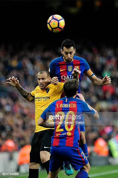 Sergio Busquets and Sergi Roberto of FC Barcelona compete for the ball with Sandro Ramírez of Malaga CF during the Spanish League match between FC...