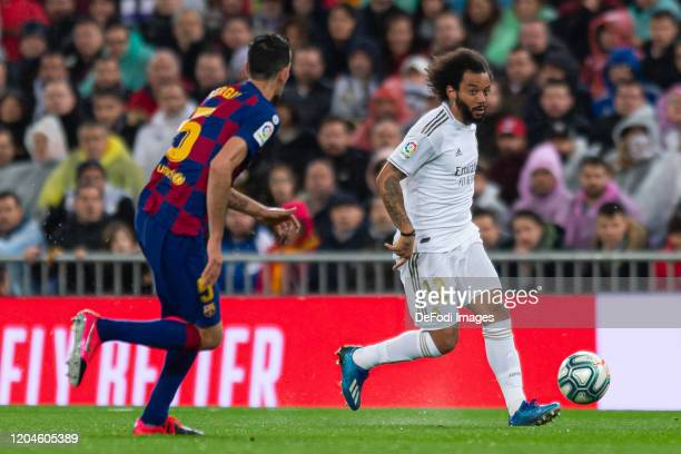 Sergio Busquets of FC Barcelona and Marcelo of Real Madrid battle for the ball during the Liga match between Real Madrid CF and FC Barcelona at...