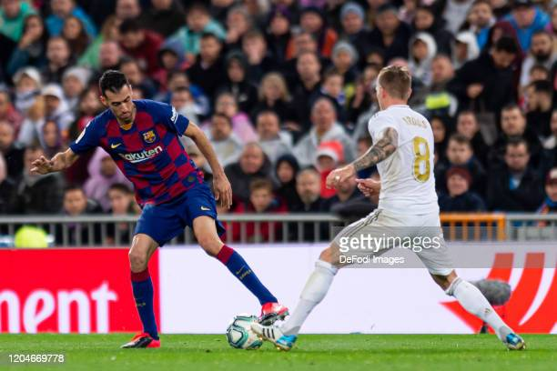Sergio Busquets of FC Barcelona and Toni Kroos of Real Madrid battle for the ball during the Liga match between Real Madrid CF and FC Barcelona at...