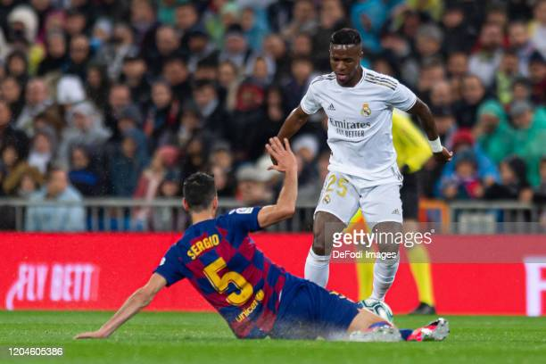 Sergio Busquets of FC Barcelona and Vinicius Jr of Real Madrid battle for the ball during the Liga match between Real Madrid CF and FC Barcelona at...