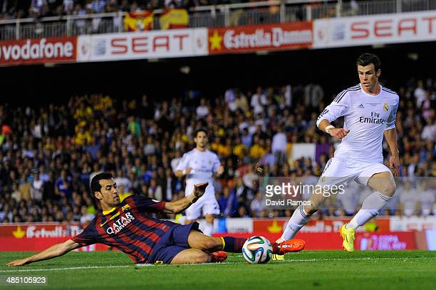 Sergio Busquets of FC Barcelona clears the ball under pressure from Gareth Bale of Real Madrid CF during the Copa del Rey Final between Real Madrid...