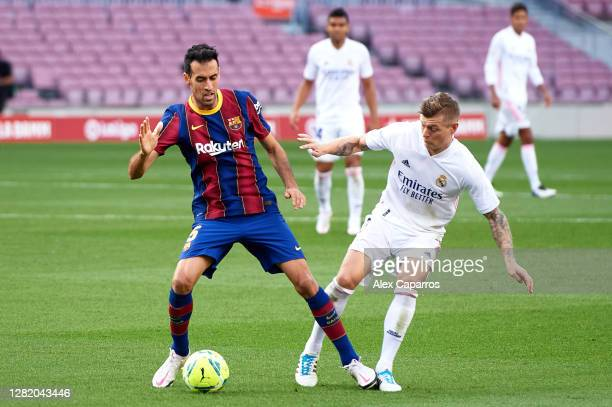 Sergio Busquets of FC Barcelona controls the ball under pressure from Toni Kroos of Real Madrid CF during the La Liga Santander match between FC...