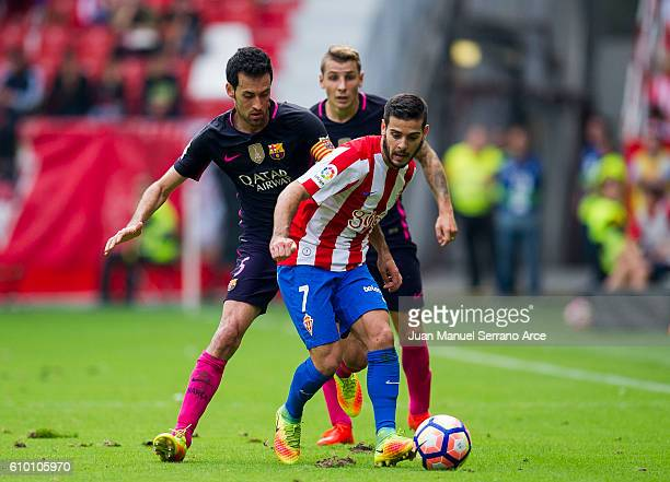 Sergio Busquets of FC Barcelona duels for the ball with Victor Rodriguez of Real Sporting de Gijon during the La Liga match between Real Sporting de...