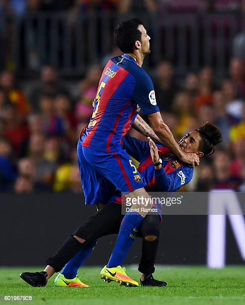 Sergio Busquets of FC Barcelona holds a young FC Barcelona supported who run into the pitch during the La Liga match between FC Barcelona and...
