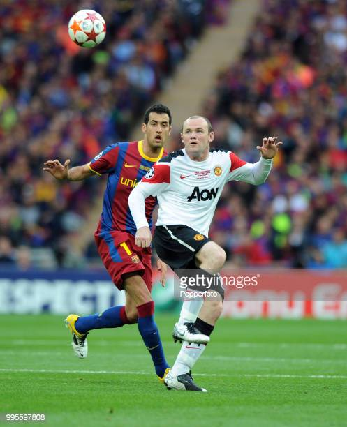 Sergio Busquets of FC Barcelona moves in to challenge Wayne Rooney of Manchester United during the UEFA Champions League final between FC Barcelona...