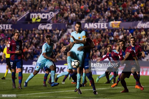 Sergio Busquets of FC Barcelona shoots on goal under pressure from Jefferson Lerma of Levante UD during the La Liga match between Levante UD and FC...