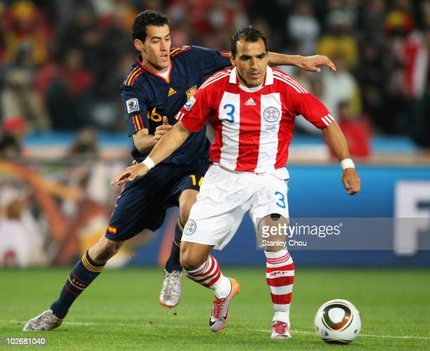 Sergio Busquets of Spain and Claudio Morel of Paraguay tussle for the ball during the 2010 FIFA World Cup South Africa Quarter Final match between...