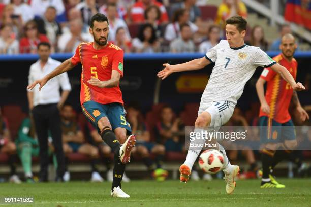 Sergio Busquets of Spain and Daler Kuziaev of Russia compete for the ball during the 2018 FIFA World Cup Russia Round of 16 match between Spain and...