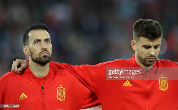 Sergio Busquets of Spain and Gerard Pique of Spain look on during the national anthems prior to the 2018 FIFA World Cup Russia group B match between...