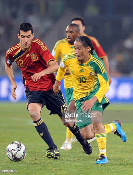 Sergio Busquets of Spain and Steven Pienaar of South Africa compete during the FIFA Confederations Cup match between Spain and South Africa at Free...