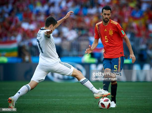 Sergio Busquets of Spain competes for the ball with Daler Kuziaev of Russia during the 2018 FIFA World Cup Russia Round of 16 match between Spain and...