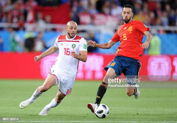 Sergio Busquets of Spain competes with Noureddine Amrabat of Morocco during the 2018 FIFA World Cup Russia group B match between Spain and Morocco at...