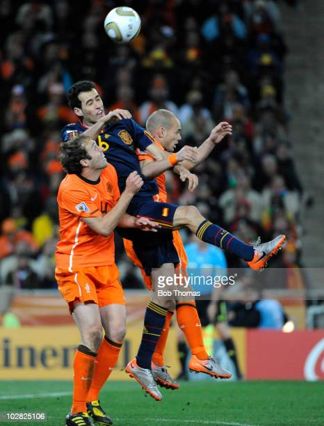 Sergio Busquets of Spain heads the ball with Joris Mathijsen and Wesley Sneijder of the Netherlands during the 2010 FIFA World Cup Final between the...