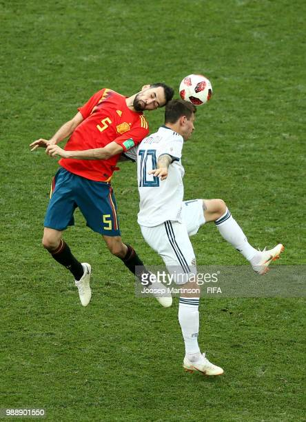 Sergio Busquets of Spain wins a header over Fedor Smolov of Russia during the 2018 FIFA World Cup Russia Round of 16 match between Spain and Russia...
