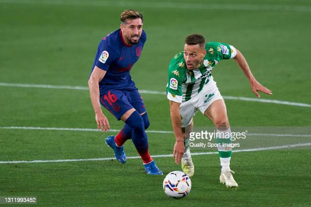 Sergio Canales of Real Betis competes for the ball with Hector Herrera of Atletico de Madrid during the La Liga Santander match between Real Betis...