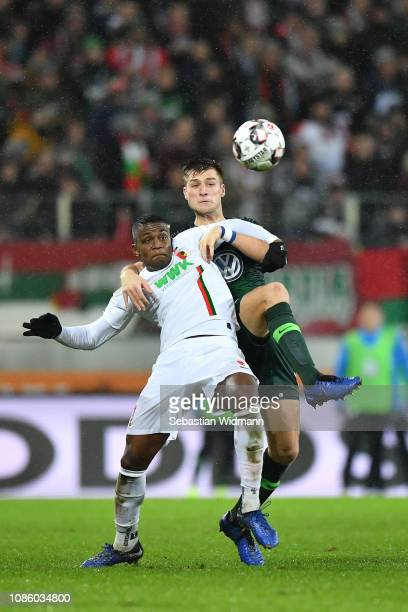 Sergio Cordova of Augsburg and Robin Knoche of Wolsburg compete for the ball during the Bundesliga match between FC Augsburg and VfL Wolfsburg at...