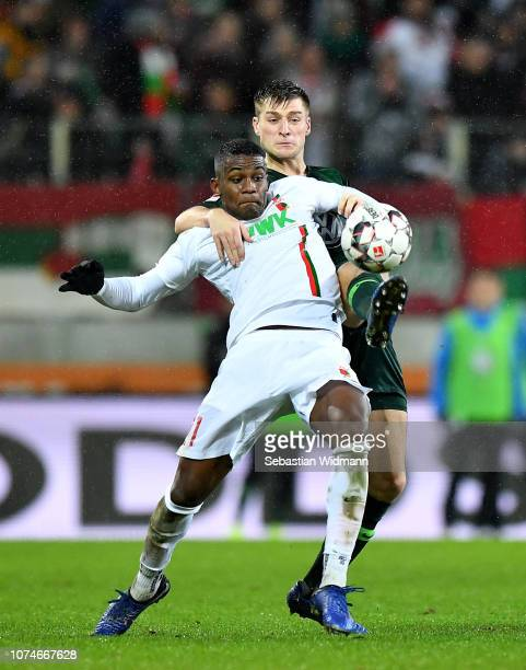 Sergio Cordova of Augsburg and Robin Knoche of Wolsburg during the Bundesliga match between FC Augsburg and VfL Wolfsburg at WWKArena on December 23...