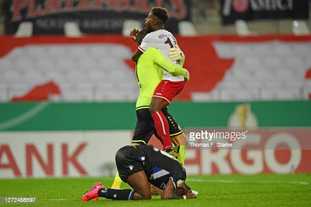 Sergio Cordova of Bielefeld looks dejected while Daniel Davari and Daniel Heber of Essen clebrate after the DFB Cup first round match between...