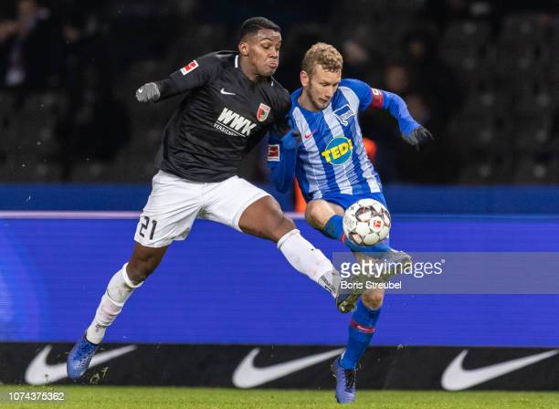 Sergio Cordova of FC Augsburg is challenged by Fabian Lustenberger of Hertha BSC during the Bundesliga match between Hertha BSC and FC Augsburg at...