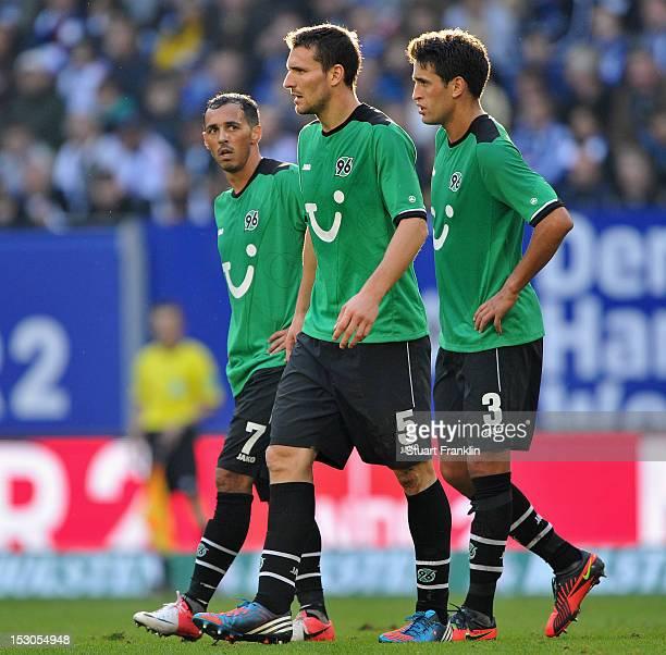 Sergio da Silva Pinto Mario Eggimann and Karim Haggui of Hannover look dejected during the Bundesliga match between Hamburger SV and Hannover 96 at...