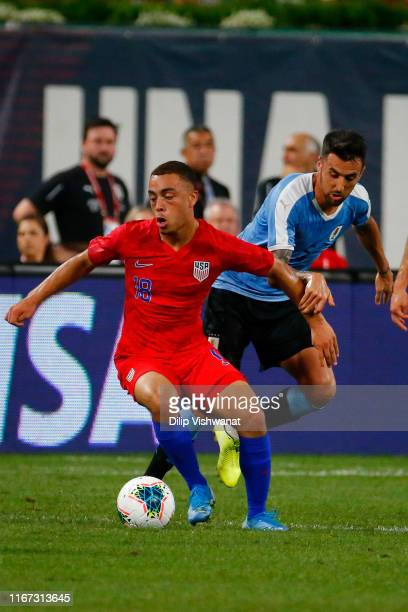 Sergiño Dest of the United States Mens National Team beats Matías Vecino the Uruguay Men's National Team to the ball during a at Busch Stadium on...