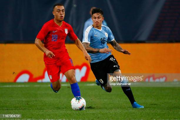 Sergiño Dest of the United States Mens National Team looks to beat Brian Rodriguez the Uruguay Men's National Team tot he ball at Busch Stadium on...