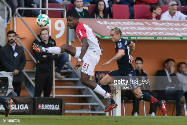 Sergio Duvan Cordova Lezama of Augsburg and Rafinha of Muenchen battle for the ball during the Bundesliga match between FC Augsburg and FC Bayern...