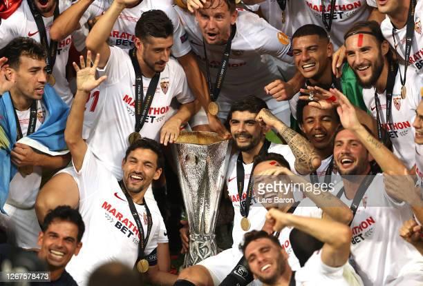 Sergio Escudero, Jesus Navas, and Ever Banega of Sevilla celebrate with their teammates and the UEFA Europa League Trophy following their team's...