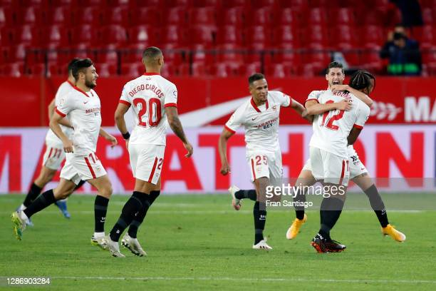 Sergio Escudero of Sevilla celebrates with teammate Jules Kounde after scoring his team's third goal during the La Liga Santander match between...