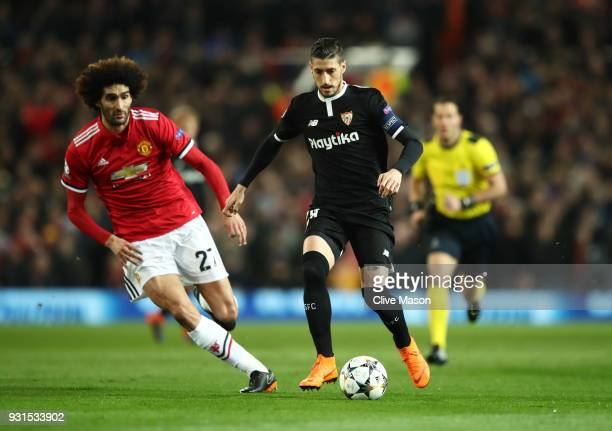 Sergio Escudero of Sevilla is chased by Marouane Fellaini of Manchester United during the UEFA Champions League Round of 16 Second Leg match between...