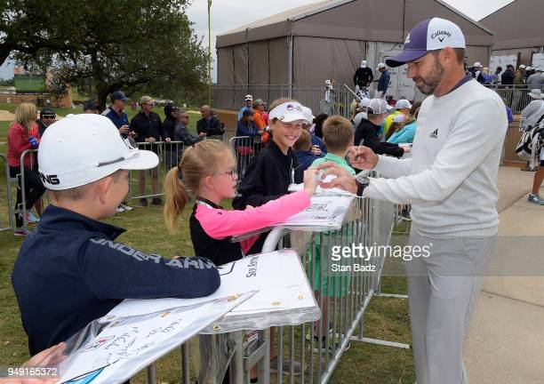 Sergio Garcia hands an autograph golf ball to Claire Grimes in the kids zone during the second round of the Valero Texas Open at TPC San Antonio ATT...
