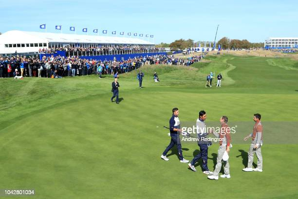 Sergio Garcia of Europe and Rory McIlroy of Europe shake hands with Tony Finau of the United States and Brooks Koepka of the United States following...