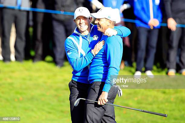 Sergio Garcia of Europe is congratulated by Rory McIlroy after he chipped in from a bunker on the 4th hole during the Morning Fourballs of the 2014...