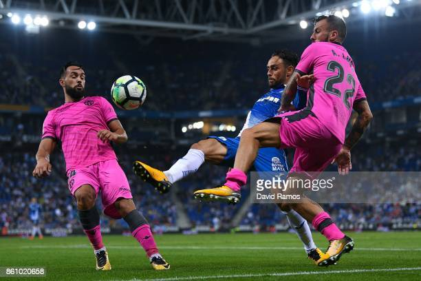 Sergio Garcia of RCD Espanyol competes for the ball with Ivi Lopez and Antonio Luna of Levante UD during the La Liga match between Espanyol and...