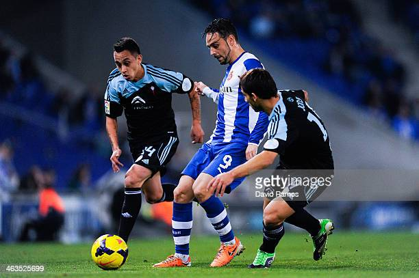 BARCELONA SPAIN JANUARY 18 Sergio Garcia of RCD Espanyol duels for the ball with Fabian Orellana and Jonny Castro of RC Celta de Vigo during the La...