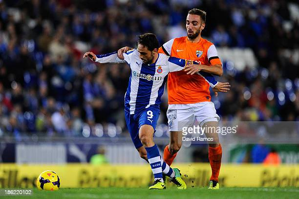 Sergio Garcia of RCD Espanyol duels for the ball with Sergi Darder of Malaga CF during the La Liga match between RCD Espanyol and Malaga CF at...